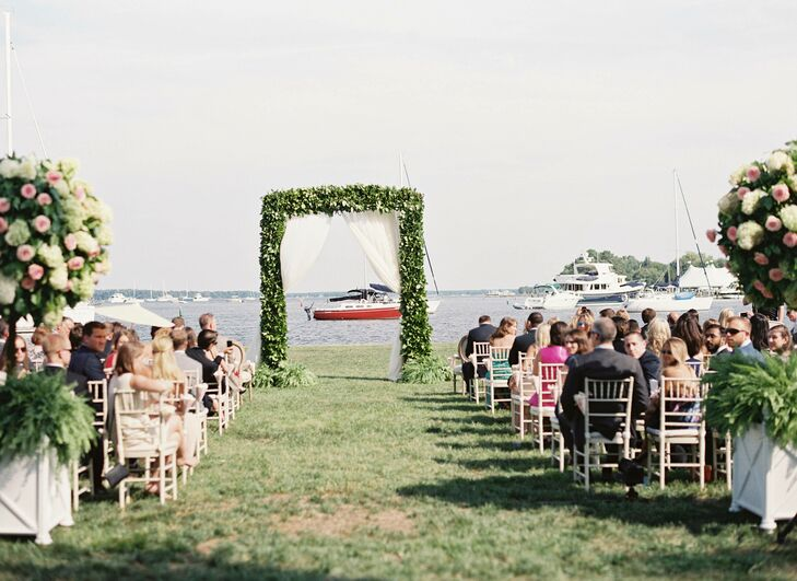 Overlooking the water, the ceremony site was decorated with vintage furniture rentals and a lush boxwood arbor with sheer curtains.