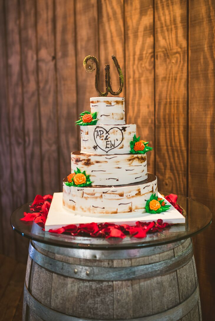 """It doesn't get more rustic than this! Ashley and Eric worked with Palermo's Bakery to design a four-tier, round, strawberry and lemon wedding cake that resembled birch wood. Each buttercream-frosted layer mimicked their wooden accents and was even paired with bright orange sugar roses. A sweet wooden """"W"""" also topped the confection. Those who dislike cake weren't left behind. A plate of homemade doughnuts was set on each table."""
