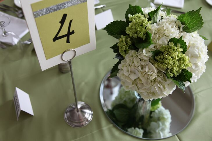 Matching the bride's bouquet, the centerpieces were made of green lady's mantle and white hydrangea. The green table numbers matched the programs with a silver strip along the top.