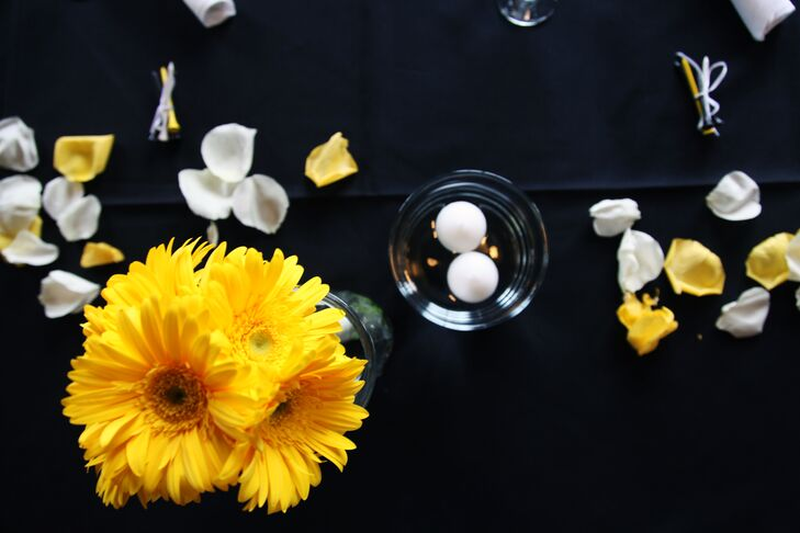 The reception tables were decorated with black linens, yellow gerbera daisies, white rose petals and floating candles.