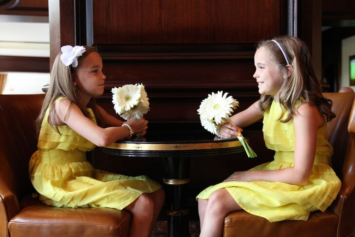 The flower girls wore yellow dresses and carried bouquets of white gerbera daisies to complement the look of the bridesmaids.