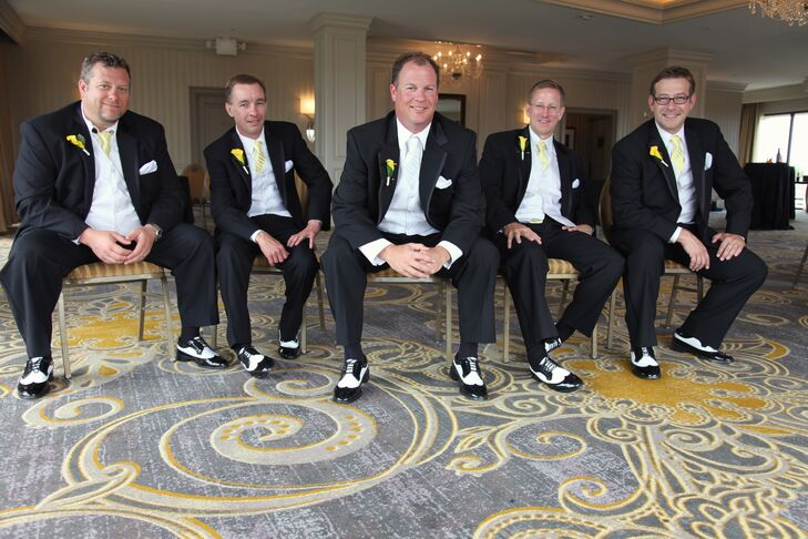 The groom and groomsmen wore black-and-white tuxedos and wingtip shoes for a classic, formal look. They wore yellow calla lily boutonnieres to match the wedding colors.