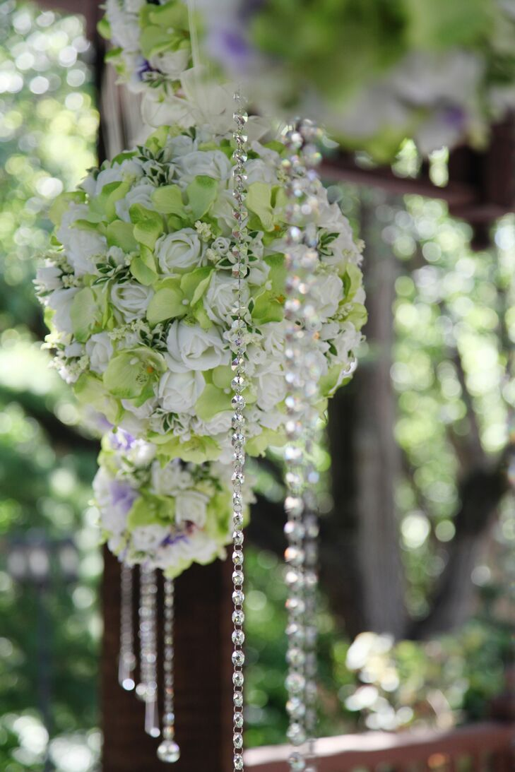 Green and white flower balls and strings of crystals decorated the ceremony site.