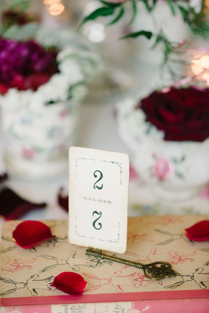 """Sarah and Steve also wanted to acknowledge the Queen of Hearts and her henchmen. They marked each reception table with a black-and-white playing card worthy of the """"Alice in Wonderland"""" army. (It even had a vintage-style border.)"""