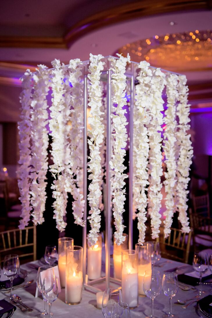 Table centerpieces included a mix of high and low floral arrangements, such as elaborate petal garlands strung from metal structures.