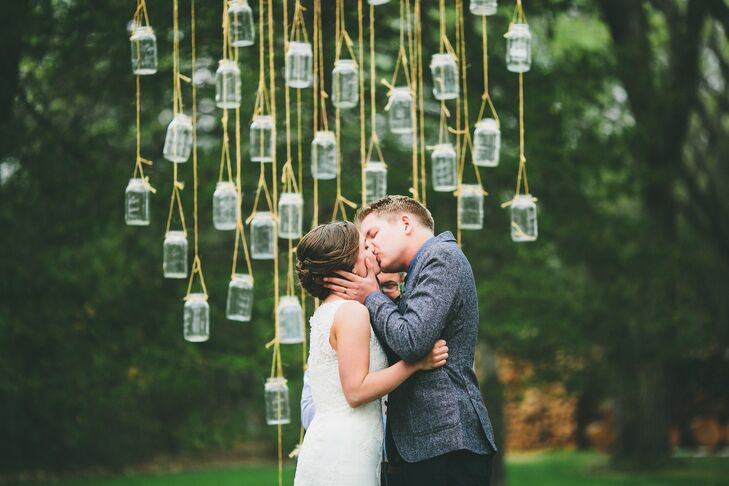 Mason jars, hung between two trees, served as a shining altar area during the outdoor ceremony.