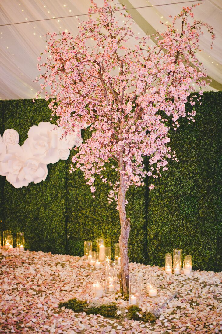 The cherry blossom trees had the floors entirely covered in its pink petals, decorating the area around the sweetheart table. Candles in glass cylinder vases that ranged in height added a romantic ambience, also scattered on the ground.