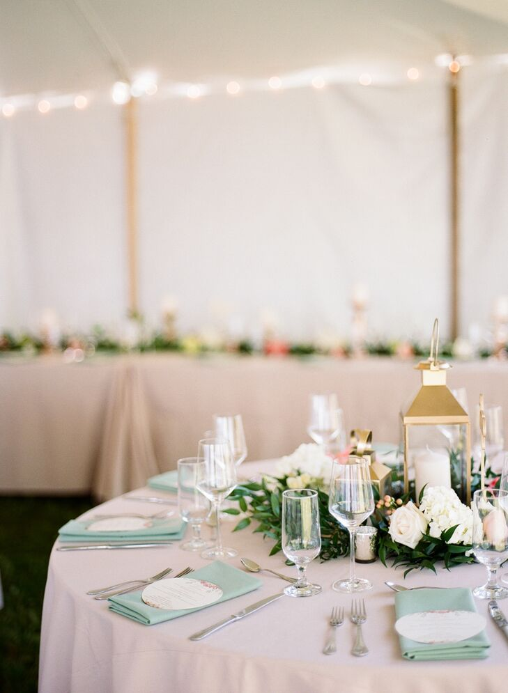 """""""We kept our flowers very simple since our location was so beautiful and lush,"""" Jamie says. """"We used lots of garlands with pops of pink peonies—my favorite flowers—and peach garden roses."""" The tablescapes also included gold lanterns, pillar candles and rose gold votives."""