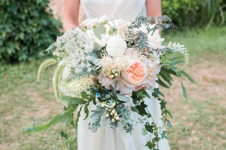 """I love dahlias, specifically cafe au lait dahlias, so I wanted them to be at the core of the floral design,"" Megan says of her textured bridal bouquet. Seagrass Florals created a cascading arrangement filled with dahlias, garden roses, peonies, spray roses, vines and wildflowers in shades of ivory, blush, blue and green."