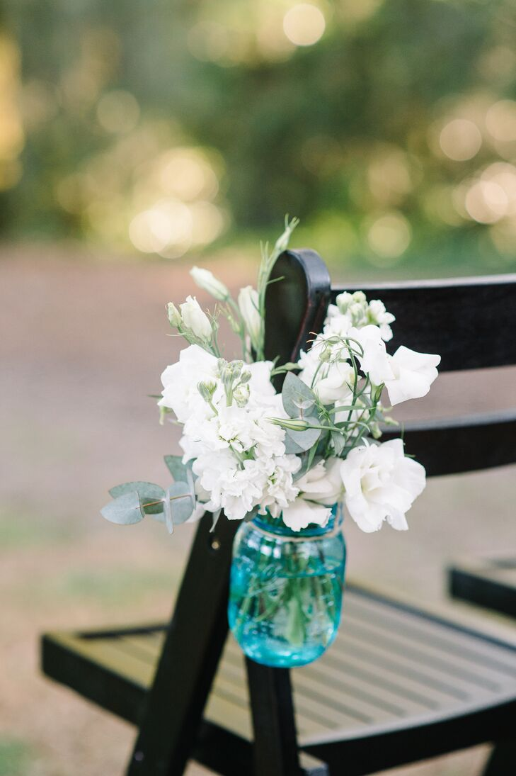 While the Legare Waring House's Row of Oaks was stunning on its own, Jaci and Kyle decided to give the outdoor space that little extra something with the addition of bunches of fresh blooms. Blue Mason jars filled with a mix of white roses, lisianthuses, stock and eucalyptus were placed on alternating rows lining the ceremony aisle.
