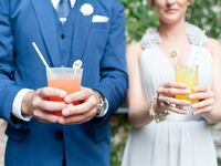 Bride and groom holding two colorful signature drinks