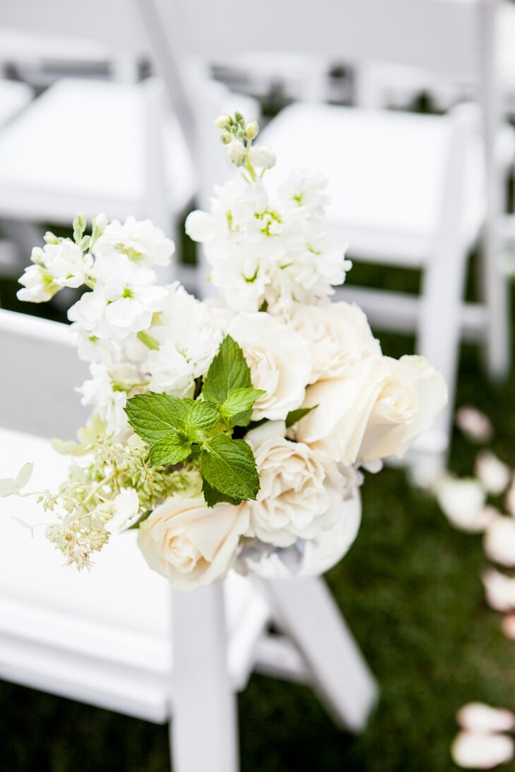 """I began with a secret garden theme,"" Kelley says. ""I wanted flowers everywhere and in various colors and sizes."" Their aisle helped to do just that with lush hanging arrangements. Ivory roses, white delphiniums and greenery in clear glass vases were placed against three rows of white chairs."