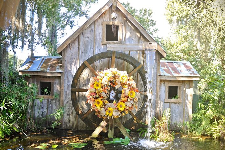 """""""As soon as I walked through the doors at Gigi's Country Garden, I knew I wanted to get married there. I didn't have to look anywhere else,"""" Heather says. """"I remember standing where our ceremony would take place with a beautiful water mill as our backdrop and looking at my fiance and saying 'This is where we will start our forever.' """" The rustic mill was decorated with a wreath of sunflowers, burlap, and fall leaves. Since burlap was all over their reception, it was the perfect accent to tie everything together."""