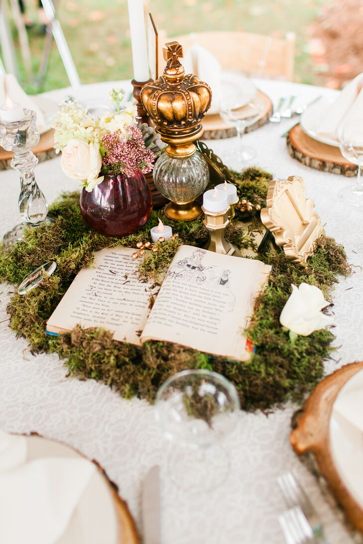 Vintage books lay on a bed of green moss to create a whimsical one-of-a-kind centerpiece.