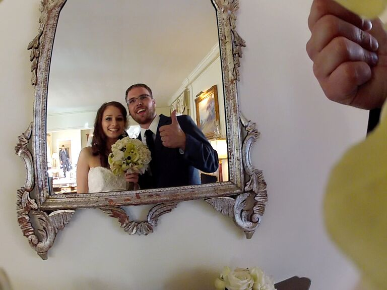 Bride and groom smiling for a hidden camera inside the bride's bouquet