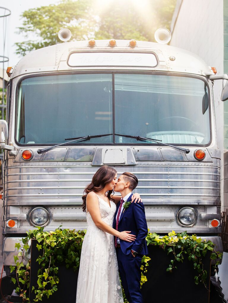 Couple standing in front of wedding bus