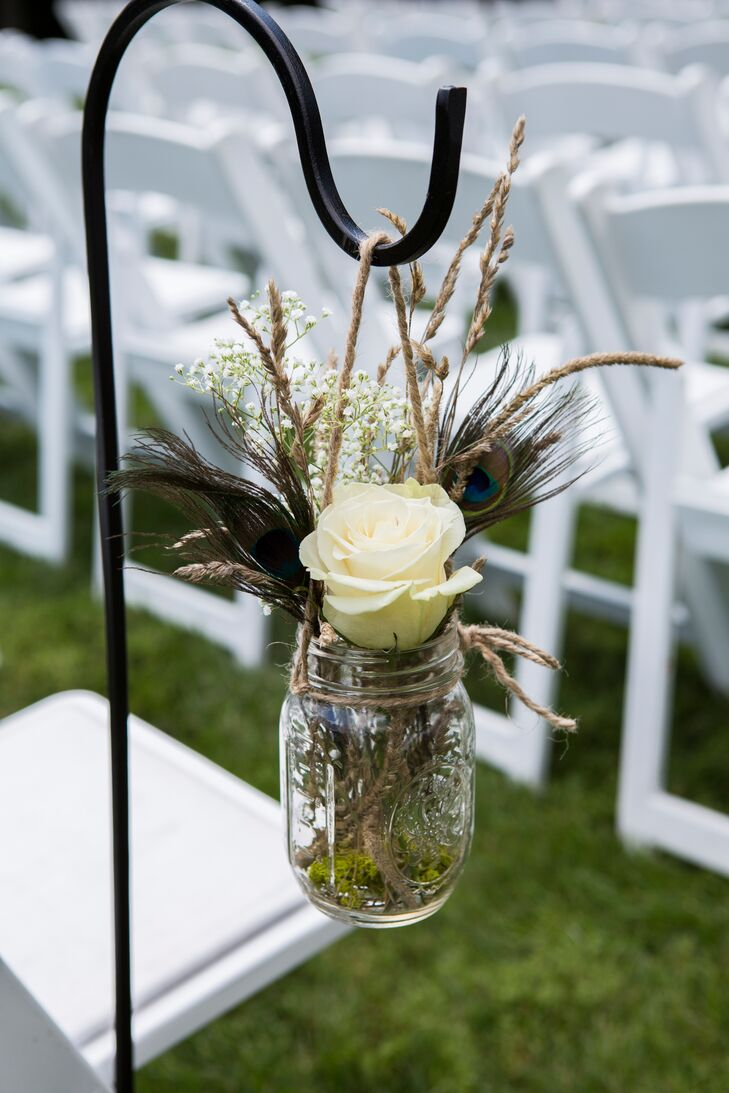 The ceremony aisle was lined with mason jars of white roses, grain grass and peacock feathers that hung from shepherds' hooks.