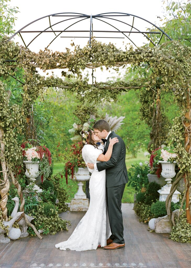 The couple married beneath a lush arbor dripped with vines and hops.
