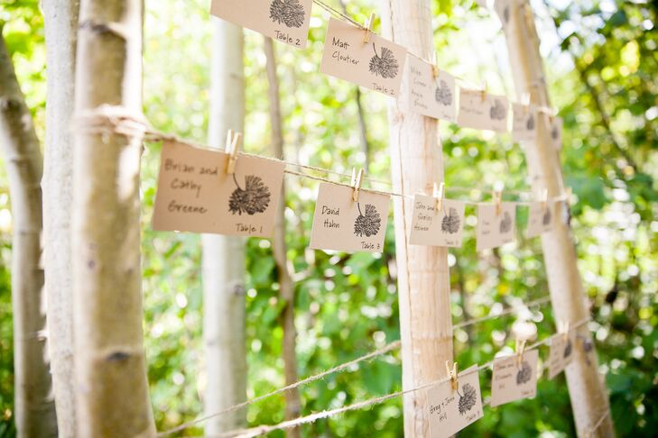 Ivory escort cards had pinecone and pine designs depicted on the paper, which hung from pieces of yarn that were tied to tree branches.