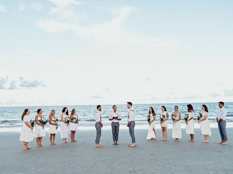 Grooms and wedding party in all-white outfits during oceanfront ceremony