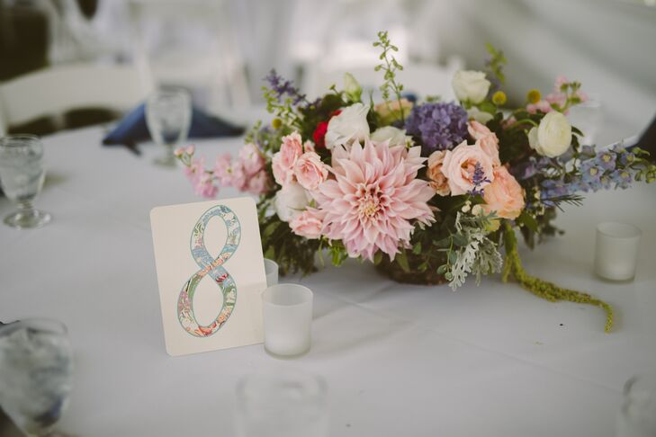 Centerpieces at the reception were made up of low, cascading flower arrangements that included pink dahlias, pink and white roses, purple hydrangeas, dusty miller and amaranthus. In keeping with the theme, the table number placards featured rosemaling prints.