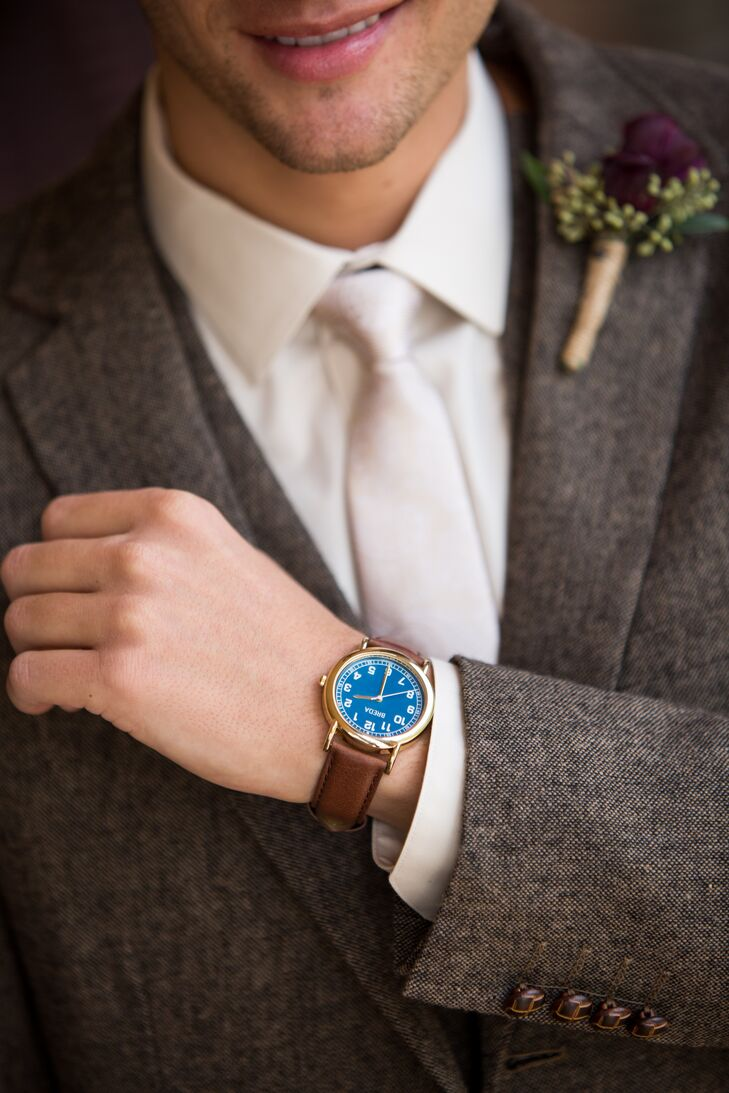 Craig had a plum-colored boutonniere to stand apart from his groomsmen (who wore white ranunculus, instead). The blue watch face on his groom's gift adds an unexpected pop of color to his neutral suit.