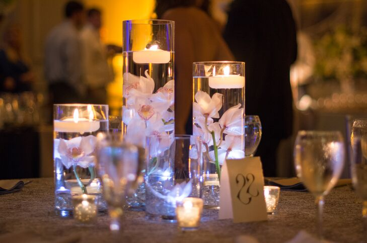 As a contrast to tall flower arrangements filled with hydrangeas, roses, stock, electric blue delphinium andrncalla lilies, certain tables were decorated with clear cylinders filled with submerged flowers.