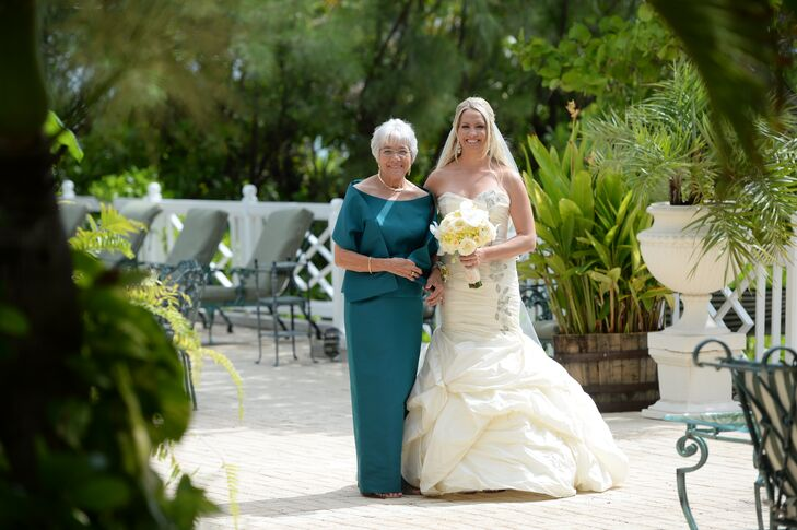 """Kristine's mother walked her down the aisle in a teal, bateau neckline, floor-length gown. Kristine's dress """"wasn't her original dress,"""" she says. """"The dress that I ended up with was a stunning Ines Di Santo dress that I bought from Bridal Reflections in New York a few weeks before my wedding."""""""