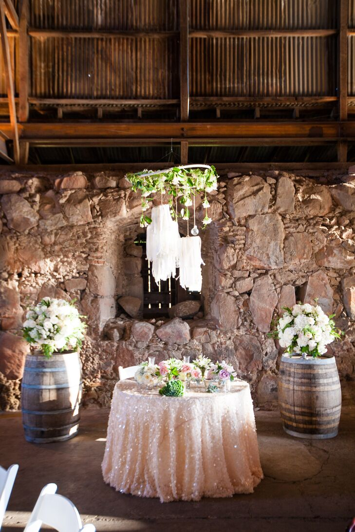 At the barn reception, Keviann and Ben sat at the sweetheart table, which was covered in a light pink glittery tablecloth and decorated with pastel-colored flowers. A whimsical chandelier hung above the table, draped in vines of white roses and white linens .