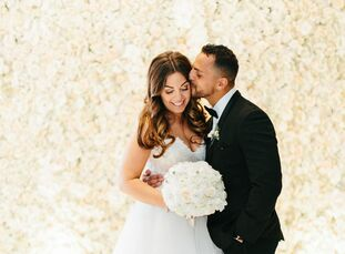 A lush flower wall, crushed white velvet aisle and sequined linens lent a glam look to Marcy Sklar (27 and a pediatric nurse manager) and George Nissa