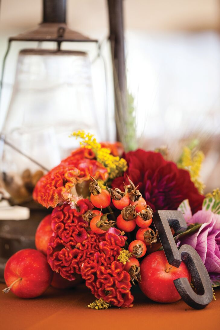 Local flowers, herbs, greens and fruits were incorporated into the centerpieces, along with wrought iron table numbers.