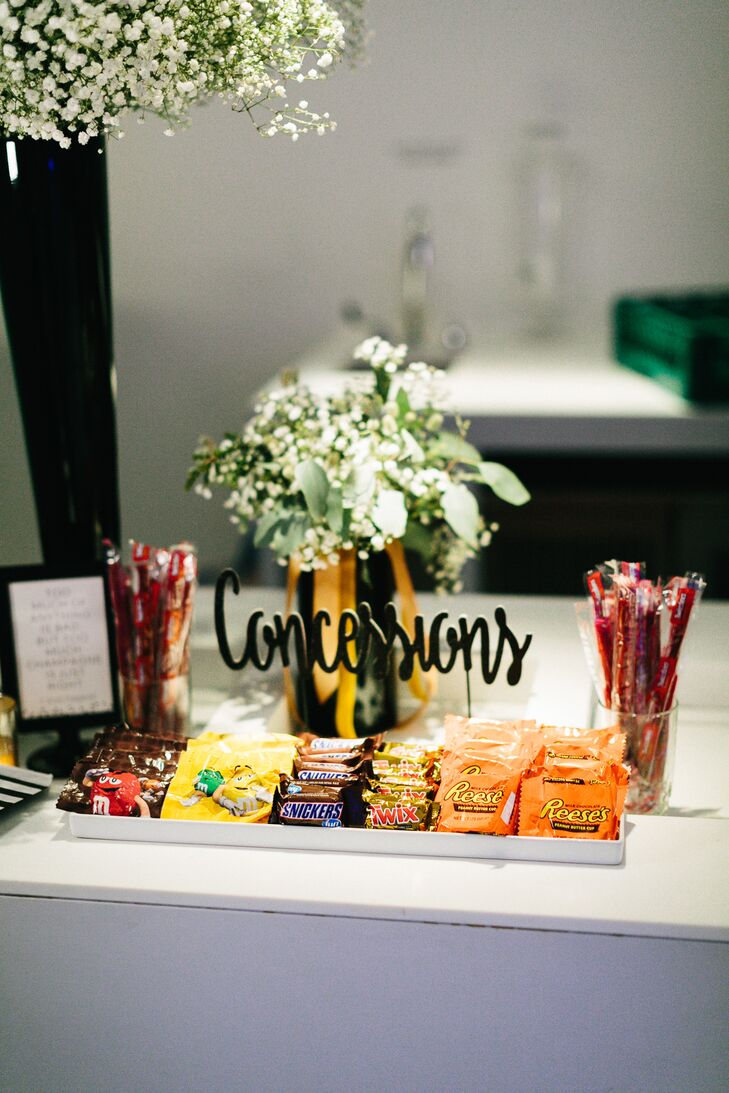 """At the end of the night, guests could stop by Liz and Adam's """"concession stand,"""" where they could indulge in the couple's favorite movie snacks, such as M&Ms, Twizzlers, Twix and Reese's Peanut Butter Cups."""