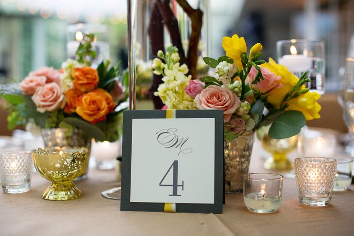 The reception tables were numbered with simple folded paper table numbers decorated with white and yellow ribbon and finished with the couple's monogram in gray calligraphy-style typography.