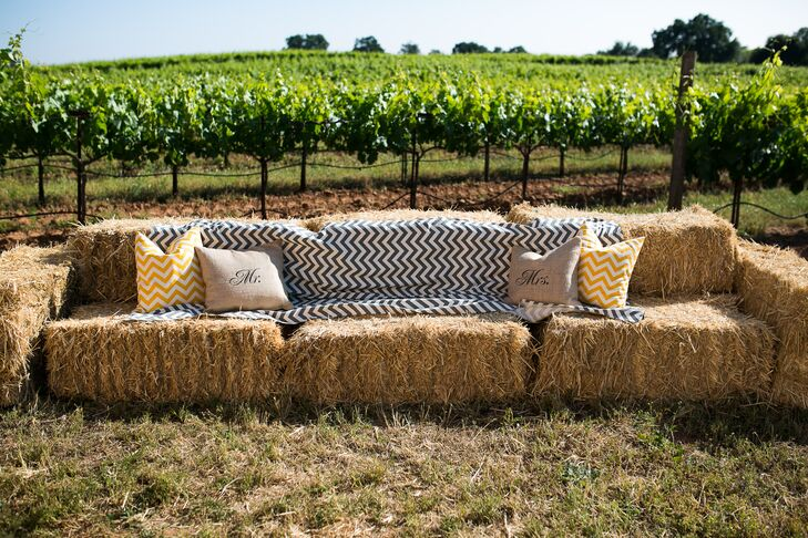 Black and white zigzag patterned linens and square pillows decorated stacks of hay bales, matching the country style and serving as lounge furniture for friends and family during the outdoor festivities.