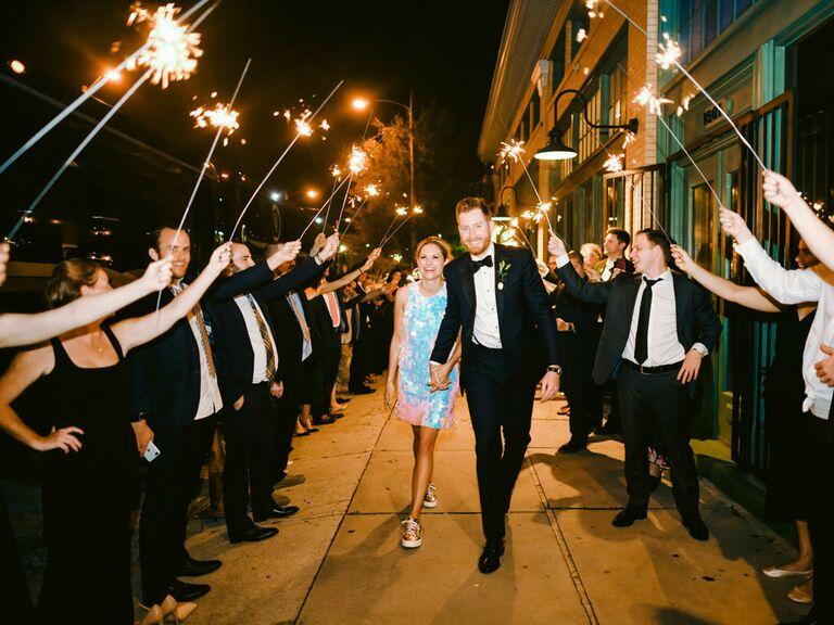 Bride and groom exiting wedding reception under sparkler tunnel