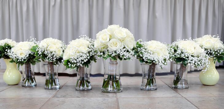 Molly and her bridesmaids carried bouquets with ivory roses and baby's breath for the summer wedding.