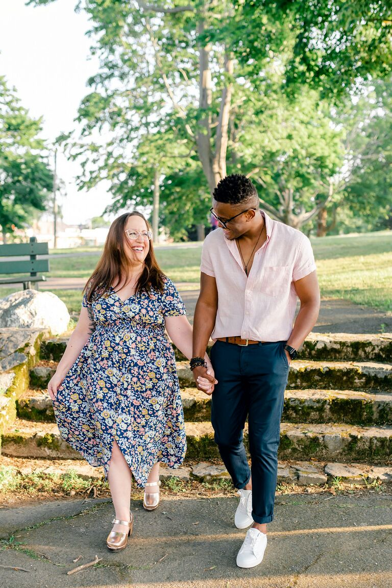 Couple walks hand-in-hand through park during sunset engagement photo shoot