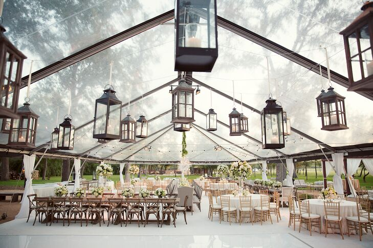 Lucy and Will's reception took place under a clear tent illuminated by string lights, lanterns and chandeliers. To maintain the natural element of their outdoor venue, Heart of the Ranch in Fort Worth, Texas, they used farmhouse tables and a mix of neutral-and-green-patterned tablecloths inside and outside the tent.