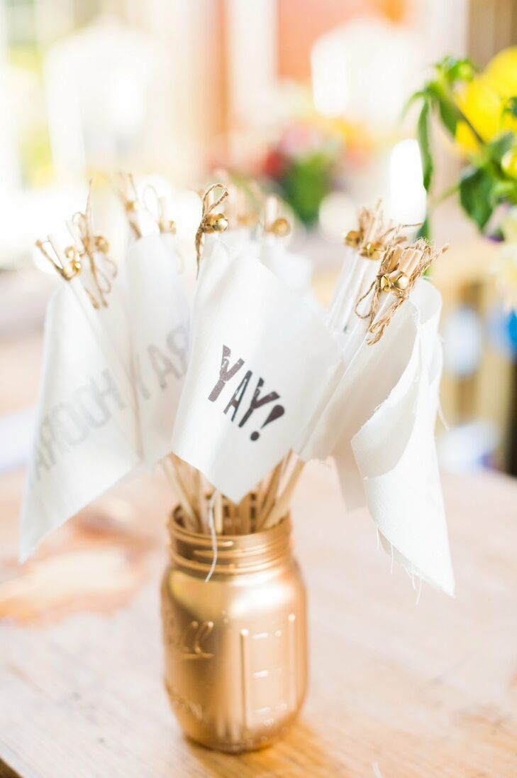 "As Samantha and Adam made their way up the aisle as husband and wife, their friends and family members waved small white flags with ""Yay!"" emblazoned on them in celebration."