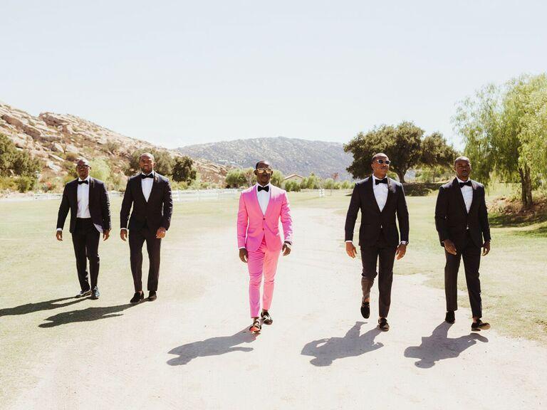 Groomsmen and groom walking into wedding reception