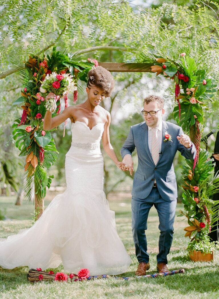 Couple jumping the broom at tropical wedding ceremony