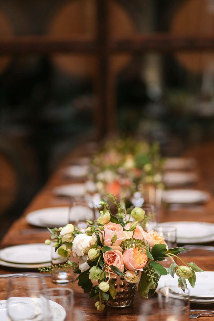 Emma and Jesse looked to bunches of textured, peach, ivory and coral flowers to bring their rustic reception tables to life. Mercury glass vases ran the length of the table, bearing cascades of roses, wildflowers, peonies, vines and leaves. To create a sense of cohesion between each of the decor elements, the pair dressed the tables with vintage floral dinnerware.