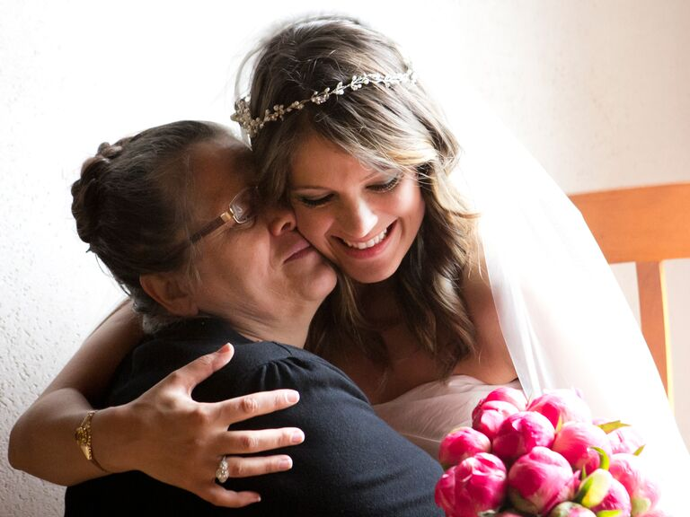 Mother of the bride and bride hug on wedding day