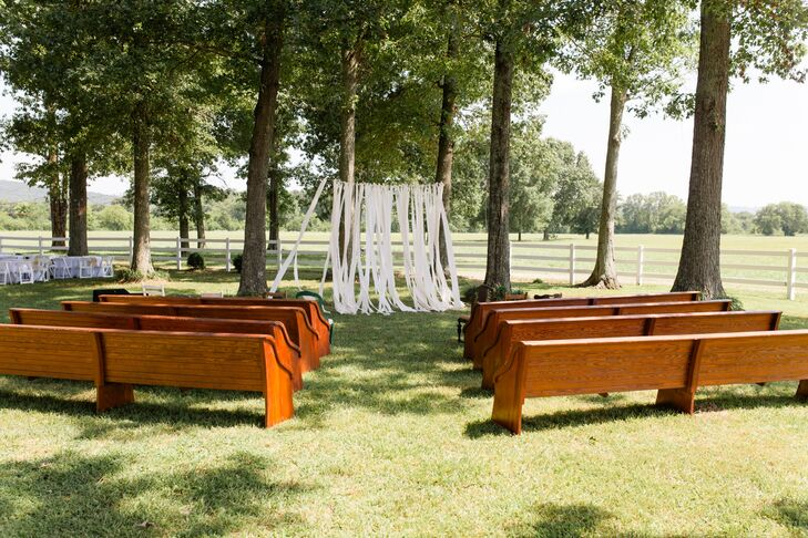 While Alix and George had intended to host only their reception at Alix's grandfather's farm, he finally convinced the couple to host the ceremony on the farm as well. He pulled a stash of salvaged church pews out of storage for the affair, setting them up in the backyard next to the spot where the reception would take place.  The couple created a simple backdrop for the ceremony to help define the space, hanging panels of flowy fabric between the tall trees.