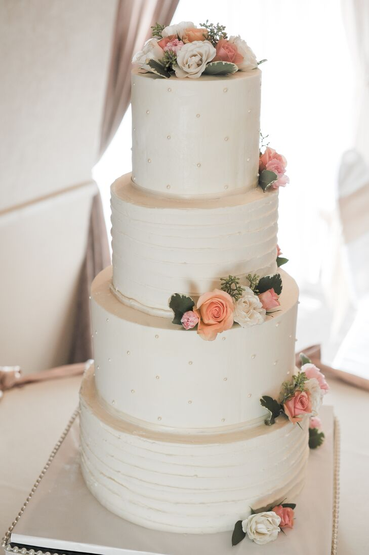 For dessert, the Gourmet Cupcake Shoppe created a four-tier wedding cake consisting of raspberry cheesecake, lemon drop, and chocolate truffle-flavored cake, satisfying every guest who had a sweet tooth. Iced with an ivory buttercream icing, real roses were added to the top and each layer to tie in the color scheme.