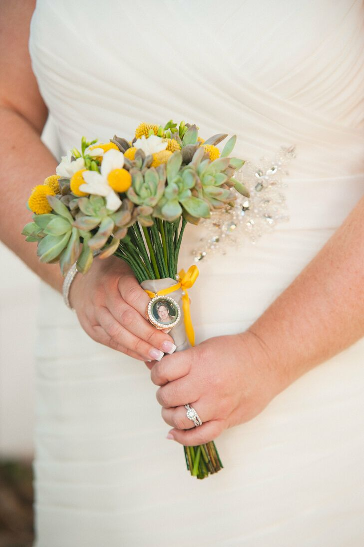 """Jonathan's Flowers brought out all three of their colors in her bouquet. Its gray ribbon wrap gathered stems of yellow craspedia, white freesias and succulents. Kimberlee also made sure her bouquet had a sentimental accent. """"I had a framed photo of my grandmother who passed away fastened to my bouquet, so she could walk down the aisle with me,"""" Kimberlee says. """"This was one of my favorite details."""""""