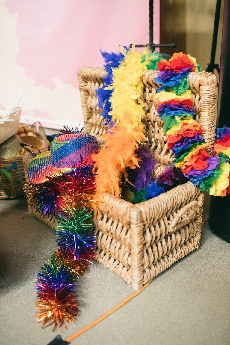 Rainbow-hued hats and boas in wicker box