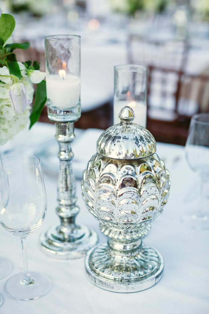 Decorative mercury-glass vases and candelabras topped reception tables.