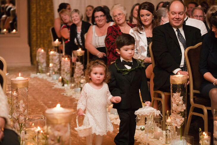 The flower girl was dressed in an ivory dress and held her basket as she walked down the ceremonial aisle with the ring bearer, who wore a classic black tuxedo with a bow tie.