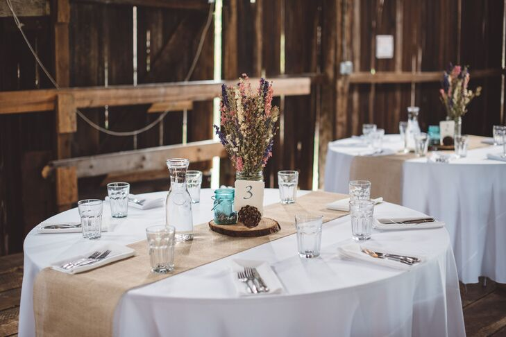 "Dining tables were dressed in white tablecloths draped with burlap runners. ""We wanted the barn to retain it'srnrustic feel while adding natural colors to the reception,"" Liza says. ""We opted for dried flowers, which my mother tirelessly arranged as well as designing the bouquets and boutonnieres for the bridal party."""